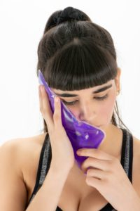 woman with purple ice pack on her cheek