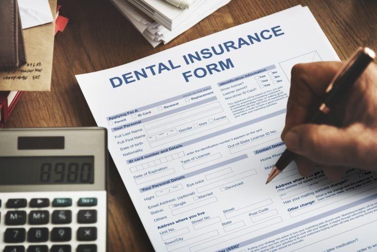 Image of a hand writing on a dental insurance form