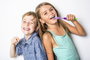 Brother and sister brushing their teeth back to back on a white background