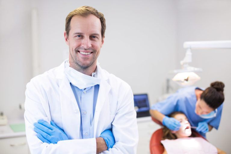 General dentist crossing his arms and smiling looking straight into the camera
